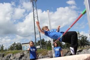 Barn som hoppar höjdhopp
